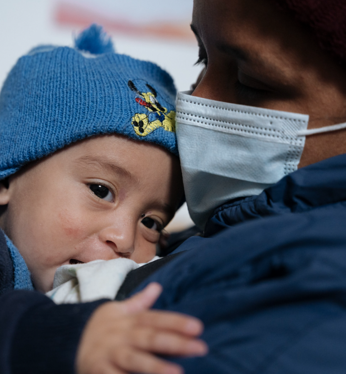 A baby in a blue hat rests on his mother who is wearing a face mask.